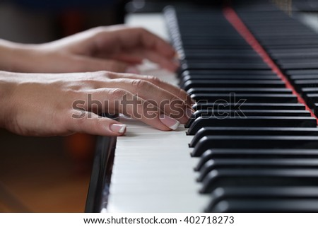 Close up of a woman playing piano. Focus is on her hand in shallow DOF. - stock photo