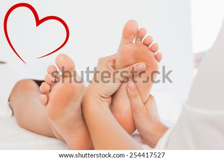 Close-up of a woman receiving foot massage against heart - stock photo