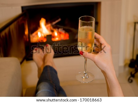 close up of a woman relaxing in front of an open wood fire drinking Champagne - stock photo