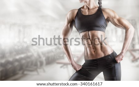Close-up of a woman's body bodybuilder in the gym - stock photo