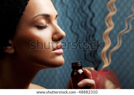 close-up of a woman's face, smelling aroma bottle - stock photo