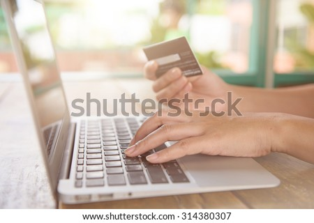 Close Up Of A woman Shopping Online Using Laptop With Credit Card - stock photo