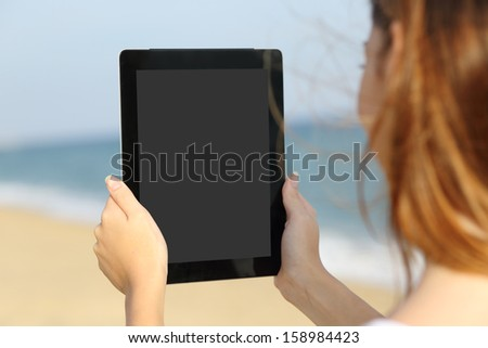 Close up of a woman showing a big blank tablet screen on the beach with the sea in the background              - stock photo