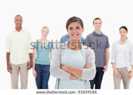 Close-up of a woman smiling and crossing her arms with people behind against white background - stock photo