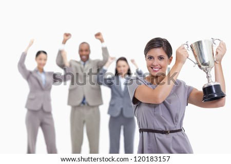 Close-up of a woman smiling and holding up a cup with co-workers raising their arms in the background - stock photo