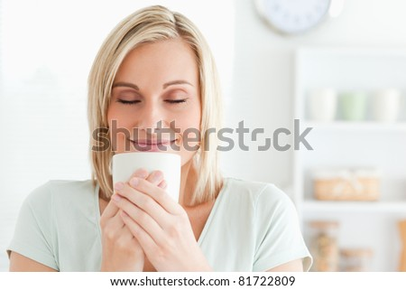 Close up of a woman taking in smell of coffee with her eyes closed in the kitchen - stock photo