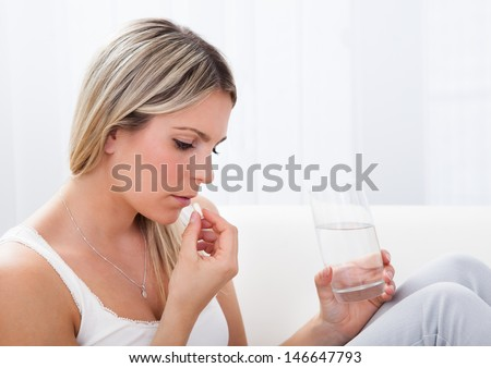 Close up of a woman taking pills holding glass of water - stock photo