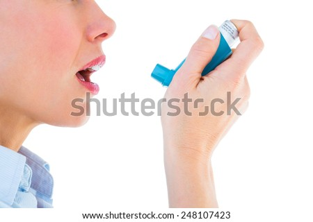 Close up of a woman using an asthma inhaler on white background - stock photo