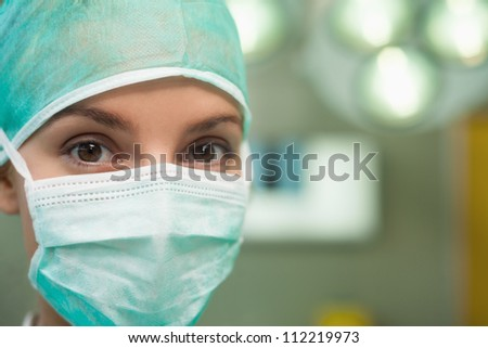 Close up of a woman wearing surgical gear in a surgical room - stock photo