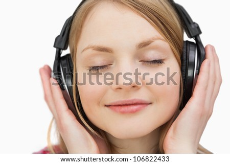 Close up of a woman with headphones against a white background - stock photo