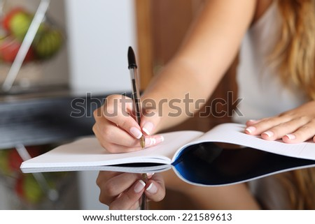 Close up of a woman writer hand writing in a notebook at home in the kitchen - stock photo