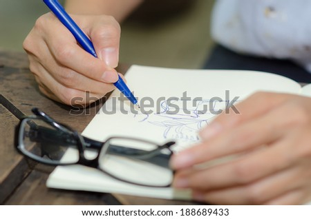 Close-up of a woman writing into her diary, in the park - stock photo