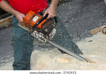 Close up of a woodcarver creating a sculpture from a pine log, using a chainsaw. Sawdust flying. - stock photo