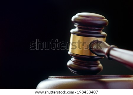 Close up of a wooden brass bound gavel for a judge or auctioneer standing upright on its base against a dark background with copyspace - stock photo
