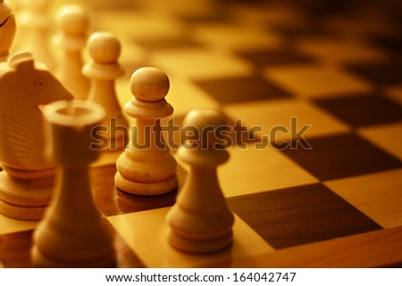 Close-up of a wooden chess table with the pieces aligned for the beginning of the game, symbol of intelligence and strategy - stock photo