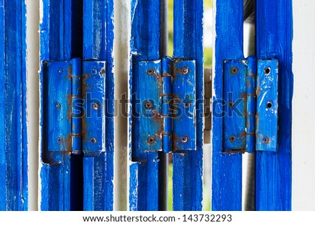 Close-up of a wooden door with blue hinge - stock photo