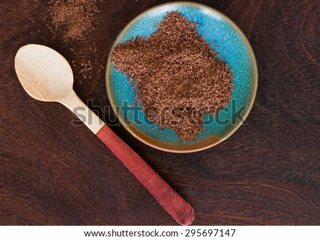 close up of  a wooden spoon and chocolate powder in a blue bowl - studio shot  from above - stock photo
