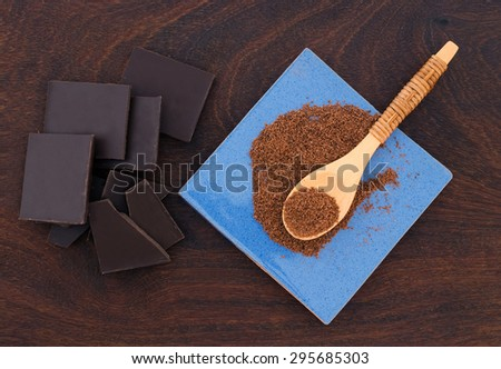 close up of  a wooden spoon, chocolate and cacao powder on wooden background - studio shot  from above - stock photo