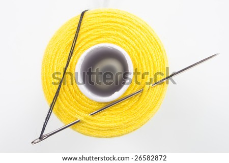 close up of a yellow sewing spool with a needle - stock photo