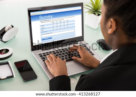 Close-up Of A Young African Businesswoman Filling Online Survey Form On Laptop - stock photo