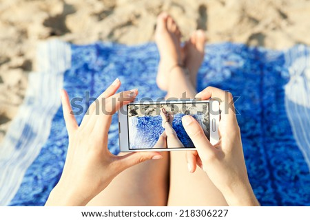 Close up of a young and attractive woman tourist hands together holding a modern technology smartphone and taking a selfie picture of her own legs while laying down on a sandy beach on holiday. - stock photo