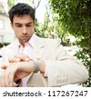 Close up of a young attractive businessman looking at the time in his watch while standing in a classic city street, outdoors. - stock photo