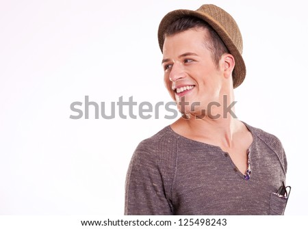 close up of a young casual man looking very happily to his side, over the shoulder, on a light background - stock photo