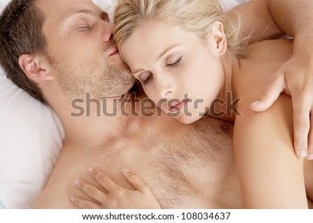 Close up of a young couple sleeping together in bed. - stock photo