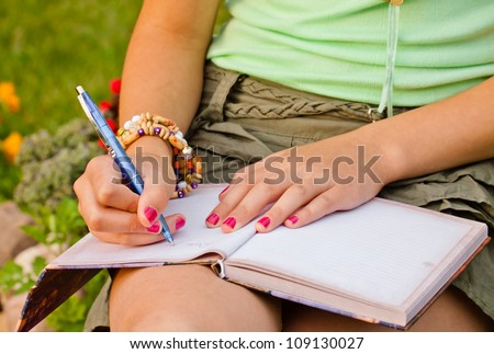 Close-up of a young girl writing into her diary, in the park - stock photo