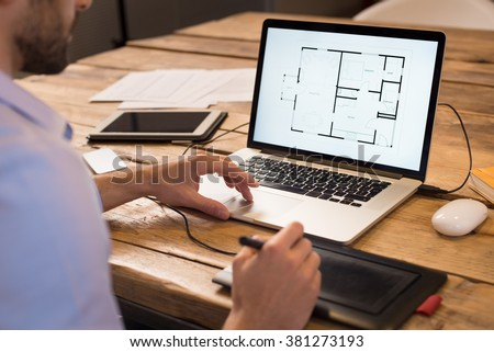 Close up of a young interior designer working in office. Architect working on laptop at new house project with graphics tablet. Interior designer studying layout of his house project on computer. - stock photo