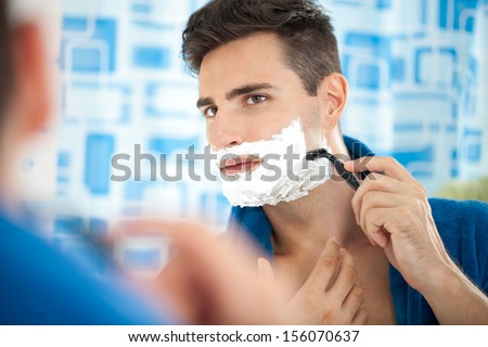 Close up of a young man shaving using a razor - stock photo