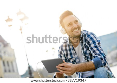 Close up of a young man sitting outdoors listening to music.He is enjoying the music. - stock photo