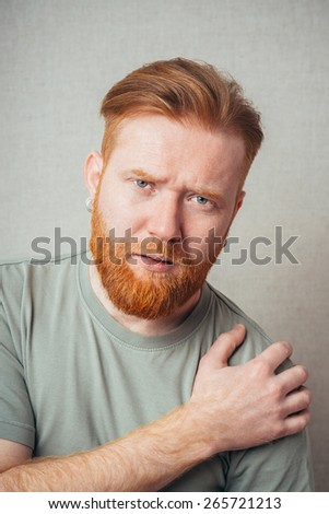 Close-up of a young man suffering from shoulder pain  - stock photo