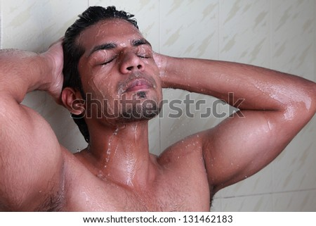 Close-up of a young man taking a shower - stock photo