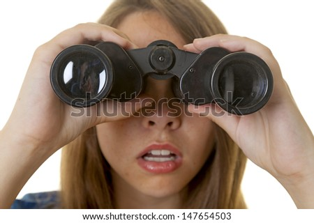 Close-up of a young observing thruough a pair of binoculars. - stock photo