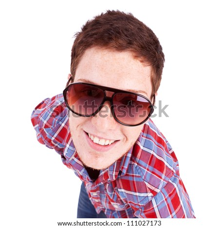 close-up of a young red-haired man wearing fancy sunglasses and smiling at the camera - stock photo