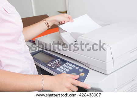 Close up of a young secretary using a copy machine - stock photo