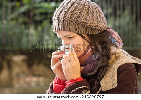Close-up of a young woman blowing nose with tissue paper at the park - stock photo