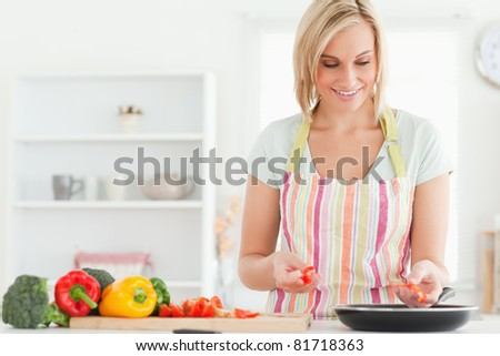 Close up of a young woman frying peppers in the kitchen - stock photo