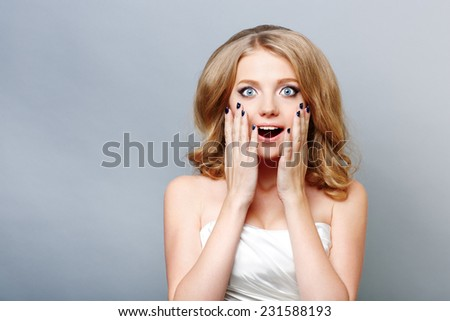 Close-up of a young woman looking surprised - stock photo