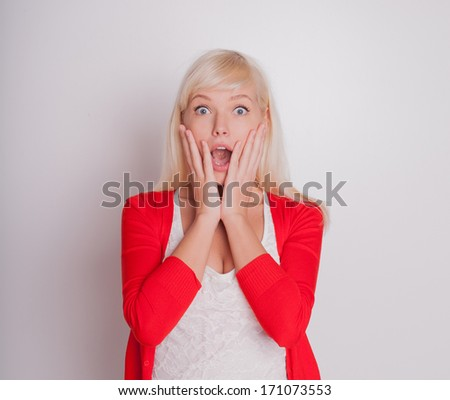 Close-up of a young woman looking surprised against white background  - stock photo