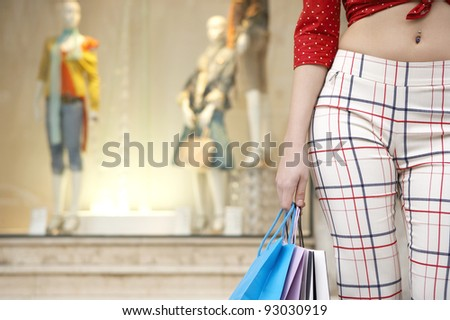 Close up of a young woman's body holding shopping bags, standing by shop window. - stock photo