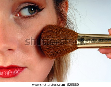 Close up of a young woman's face as she puts on blusher using a make up brush. - stock photo