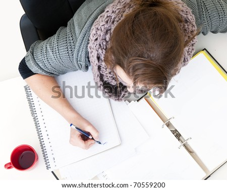 Close up of a young woman studying, seen from above - stock photo