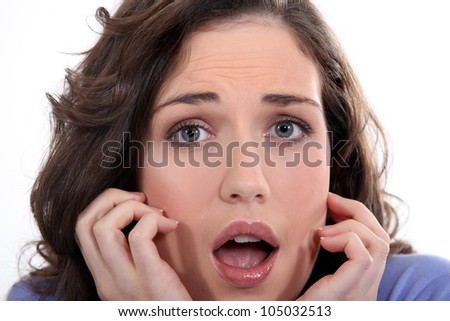 Close-up of a young woman with expression of fear - stock photo