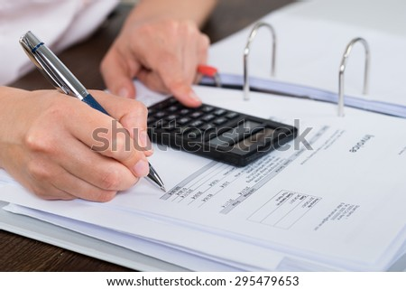 Close-up Of Accountant Doing Calculation With Calculator In Office - stock photo