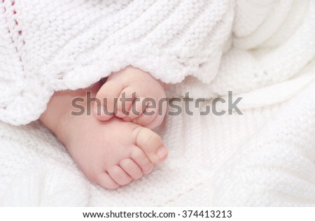 Close up of adorable baby feet on blanket - stock photo