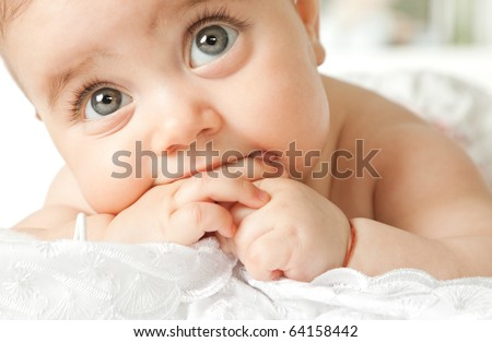 Close-up of adorable little baby face lying with hand in mouth, looking up - stock photo