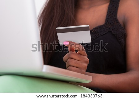Close-up Of African American woman holding credit card while shopping online at home - stock photo