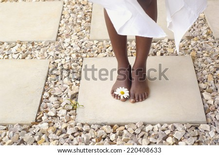 Close up of African American woman's bare feet with flower - stock photo